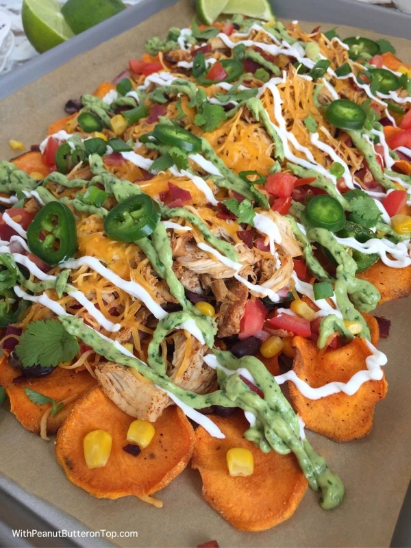 Loaded Sweet Potato Nachos with Homemade Sweet Potato Chips -the perfect tailgating appetizer! Great for a crowd of hungry people or just a family of nacho lovers. Piled high with black beans, corn, my Slow Cooker Mexican Style Shredded Chicken, and drizzled with plain greek yogurt and my Greek Yogurt Spinach Guacamole atop hearty, crispy homemade sweet potato chips. #nachos #healthy #appetizer | www.withpeanutbutterontop.com