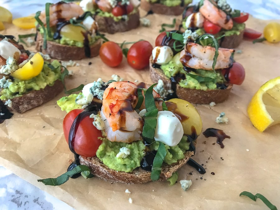 This Lemon Shrimp and Avocado Caprese is made with fresh mozzarella cheese, avocado, basil, blue cheese, heirloom tomato medley, and wild caught shrimp. Full of flavor, absolutely refreshing and only 202 calories per slice. #shrimp #lemonshrimp #caprese #avocado #capresetoast #healthy | https://withpeanutbutterontop.com