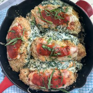 Spinach and Cream Cheese Stuffed Chicken Parmesan- this baked chicken recipe is the bomb when it comes to flavor! The chicken is stuffed with spinach and cream cheese and coated with a crispy breadcrumb coating. Tender and juicy on the inside, crispy on the outside, and flavorful throughout. Best part? All you need is one pan. #chickenparmesan #chicken #onepan #dinner #stuffedchicken | www.withpeanutbutterontop.com