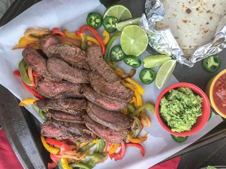 The Best and Easiest Garlic Lime Steak Fajitas - these steak fajitas are easier to make than you think and absolutely delicious! Tender marinated flat iron steak served withsautéed bell peppers, onions, and a creamy Cilantro Lime Avocado Mash. #steak #dinner #easy #steakfajitas #fajitas #mexican #onepan | www.withpeanutbutterontop.com