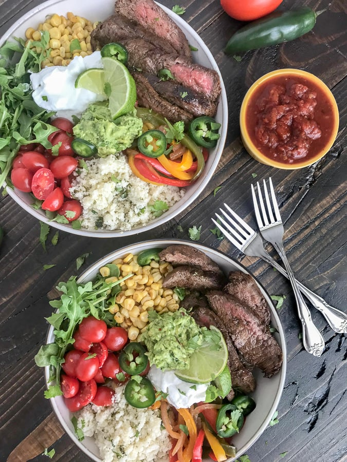 Steak Fajita Bowls with Garlic Lime Cauliflower Rice - these fajita bowls will complete your Taco Tuesday cravings! The steak is marinated in a garlic lime sauce and is super tender, as well as flavorful. #bowls #healthy #steakfajitas #fajitas   www.withpeanutbutterontop.com