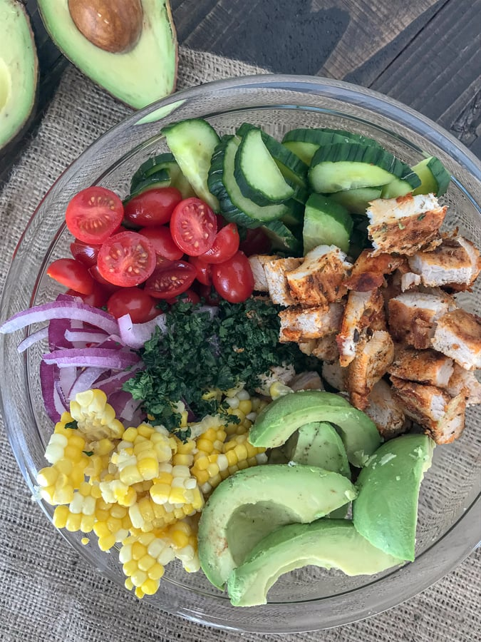 Cajun LimeChicken Avocado Corn Salad - this salad has so much flavor! Creamy, light, and drizzled with a Cilantro Lime Dressing. It is quick and easy to make and perfect for your next barbecue or get together. Light on the calories, coming in at only 203 calories per 1 cup serving. The best part? It's just as delicious the next day, making this a good meal for your to-go lunches. #avocado #salad #chickensalad #healthy   https://withpeanutbutterontop.com
