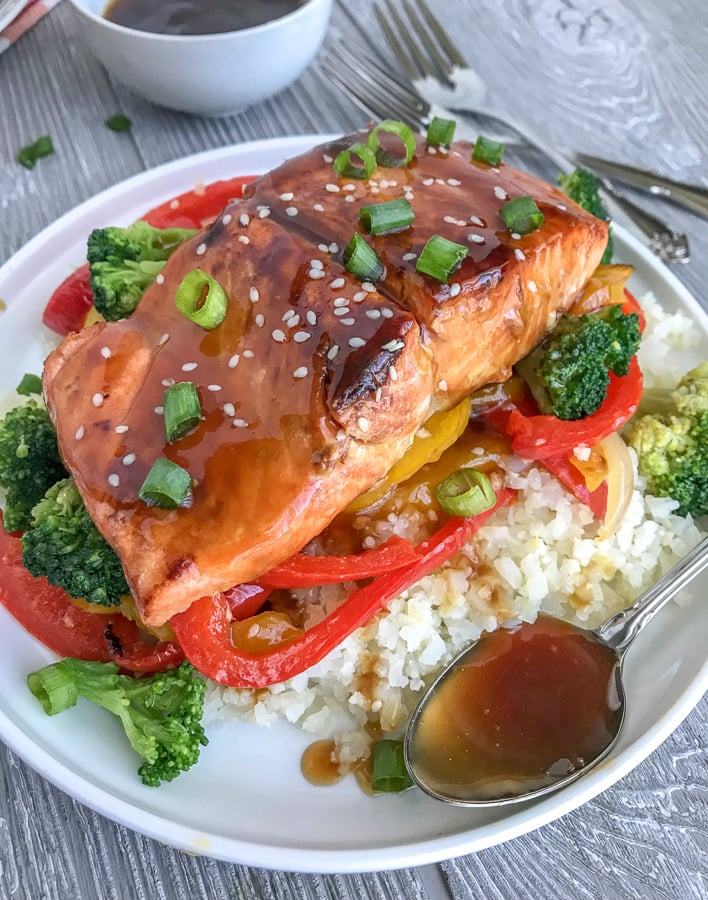 Honey Teriyaki Salmon with CauliflowerRice -a deliciously sticky, sweet and savory dish that can be on your table in under 30 minutes. Skip the high-calorie, high-carb takeout and try this healthier, low-carb rendition! #healthy #takeout #teriyaki #salmon #cauliflowerrice | https://withpeanutbutterontop.com