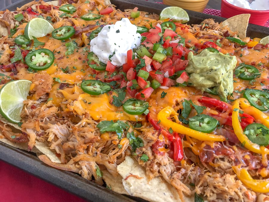 Loaded Chipotle Chicken Carnitas Nachos - more than likely the easiest, most flavor-packed nachos you will ever make! These nachos are loaded with chipotle chicken carnitas, salsa, cheese, sautéed onions and peppers, jalapeños, and topped with some amazing dips! #nachos #carnitas #loadnachos #mexican #tacotuesday #cincodemayo | https://withpeanutbutterontop.com