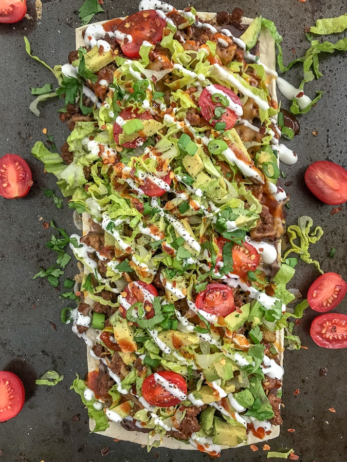 Loaded Skinny Taco Flatbread Pizza - a healthier, lower-carb version of our favorite pizza! Loaded with toppings, easy and quick to make! #pizza #tacos #tacopizza #tacotuesday | https://withpeanutbutterontop.com