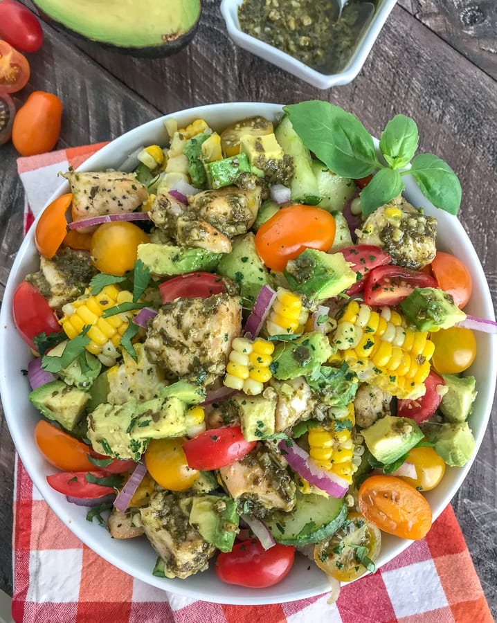 This healthy, super simple to make, and delicious Lemon Pesto Chicken Avocado Salad recipe is loaded with avocado, cherry tomatoes, red onions, corn, and the most delicious lemon pesto chicken. #salad #pestochicken #healthy   https://withpeanutbutterontop.com