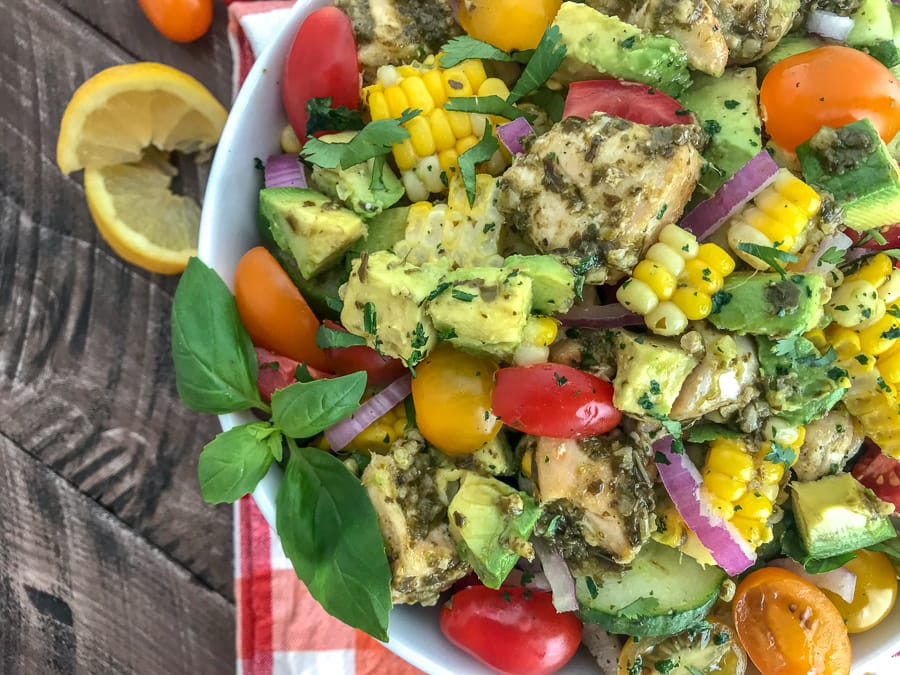 This healthy, super simple to make, and delicious Lemon Pesto Chicken Avocado Salad recipe is loaded with avocado, cherry tomatoes, red onions, corn, and the most delicious lemon pesto chicken. #salad #pestochicken #healthy | https://withpeanutbutterontop.com