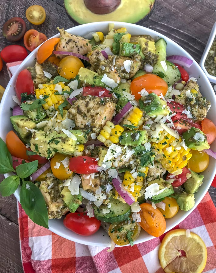 This healthy, super simple to make, and delicious Lemon Pesto Chicken Avocado Salad recipe is loaded with avocado, cherry tomatoes, red onions, corn, and the most delicious lemon pesto chicken. #healthy #pestochicken #salad   https://withpeanutbutterontop.com