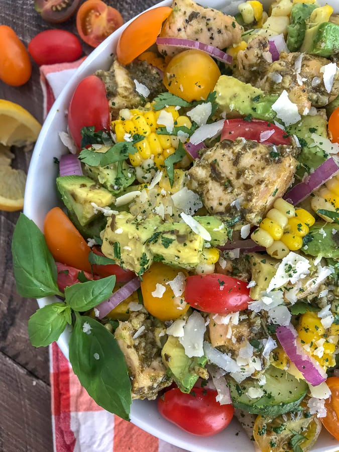 This healthy, super simple to make, and delicious Lemon Pesto Chicken Avocado Salad recipe is loaded with avocado, cherry tomatoes, red onions, corn, and the most delicious lemon pesto chicken. #healthy #pestochicken #salad | https://withpeanutbutterontop.com