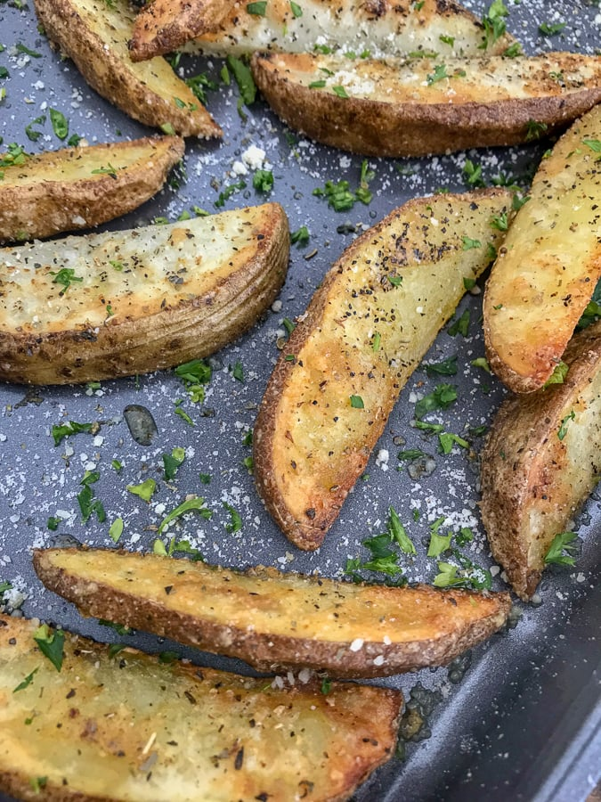 Crispy Baked Garlic Parmesan Potato Wedges - the best potato wedges you will ever try! Crispy on the outside, flaky on the inside, and flavorful throughout thanks to the garlic, parmesan seasoning! No tricks or extra work! #potatowedges #apppetizers #crispyfries | https://withpeanutbutterontop.com