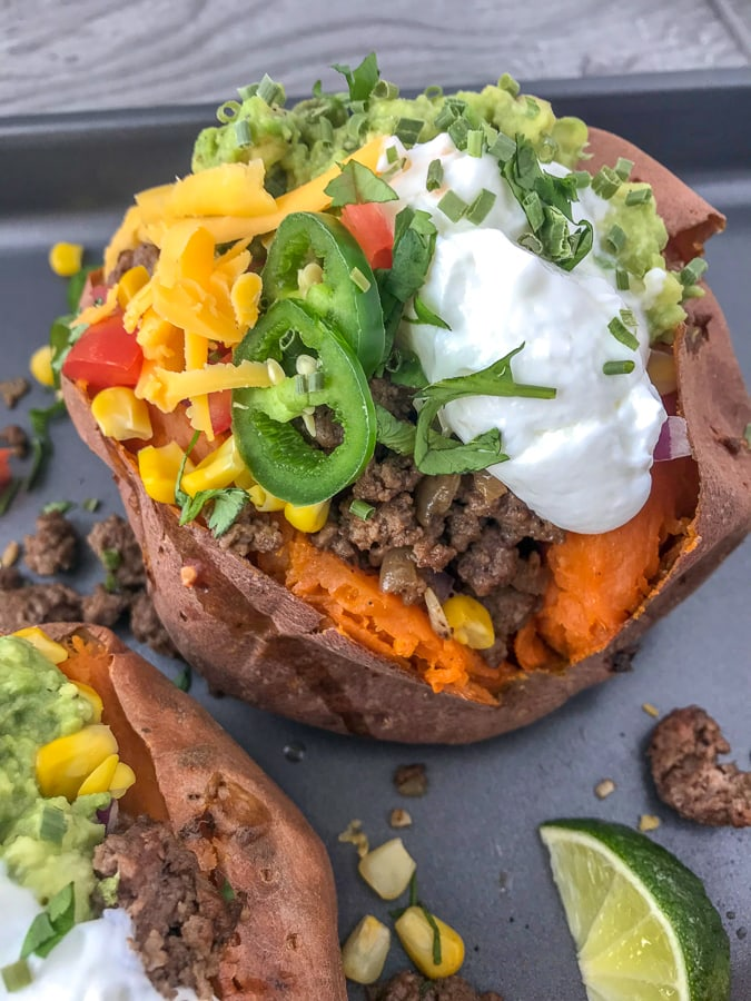 Taco Stuffed Sweet Potatoes - a simple and easy healthy spin on #TacoTuesday that you and your family are going to absolutely love! Full of flavor and perfect for those taco cravings! #taco #tacos #healthy #stuffedsweetpotatoes #tacostuffed | https://withpeanutbutterontop.com