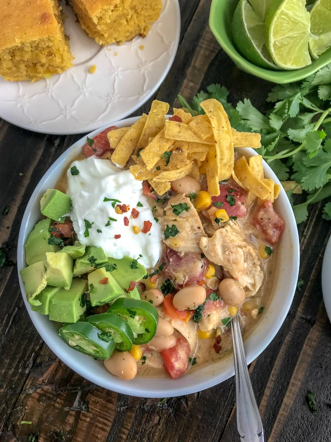 Easy One Pot White Chicken Chili - lightened up! This chili is filled with chicken breast, beans, corn, tomatoes, and that great Tex Mex flavor! Simple to make and all done in one pot! #easy #easydinners #healthy #soups | https://withpeanutbutterontop.com