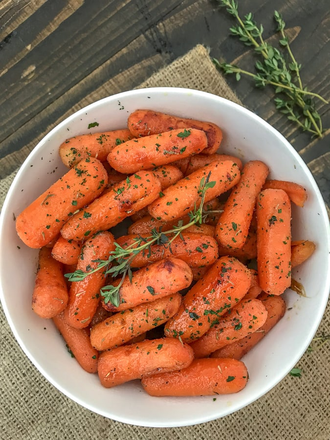 Maple Roasted Carrots - super simple and delicious side dish made with maple syrup, olive oil, and herbs. 5 minutes to prep and a great addition to any meal! #roastedcarrots #sidedish #easyrecipes #thanksgiving | https://withpeanutbutterontop.com