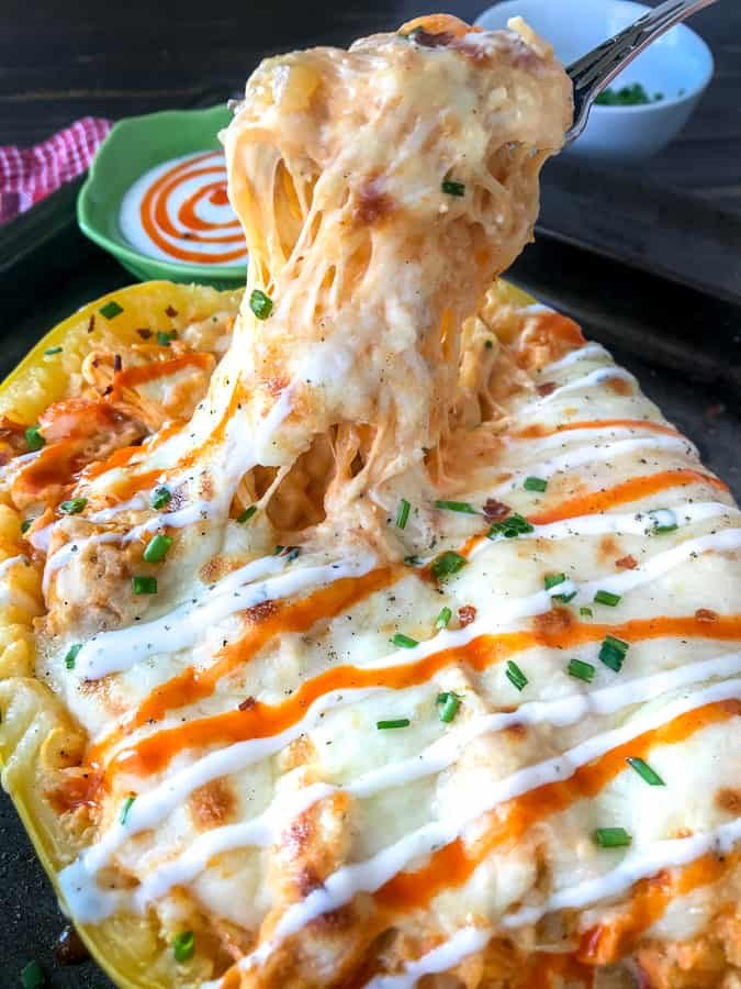 Creamy Buffalo Chicken Stuffed Spaghetti Squash - if you're a buffalo chicken and pasta fan, but are trying to cut back on the carbs - you are going to love this recipe! Spaghetti squash stuffed with shredded chicken, cheeses, sautéed peppers and onions, and a creamy buffalo sauce. Guaranteed to become a repeat meal! #buffalochicken #stuffedspaghettisquash #lowcarb | https://withpeanutbutterontop.com