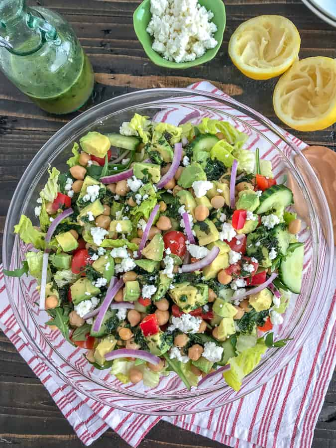 This beautiful, delicious Mediterranean Salad is an easy to throw together meal filled with crunchy cucumber, red bell peppers, onions, and chickpeas all tossed in an easy homemade vinaigrette. Sure to become a favorite #MeatlessMonday meal option! #chickpeas #salad #mediterraneansalad | https://withpeanutbutterontop.com