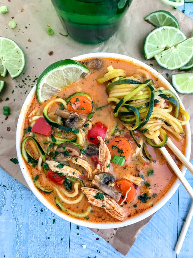 Learn how to make Thai easily and quickly at home with this ONE POT Thai Red Curry Chicken Zoodle Soup recipe! So much better than any takeout and you can control exactly what goes in it. Layers upon layers of delicious vegetables, spiralized zucchini, and tender, shredded chunks of chicken, all in a coconut red curry broth. Absolutely outstanding and delicious! #thai #takeout #lowcarb #soup   https://withpeanutbutterontop.com