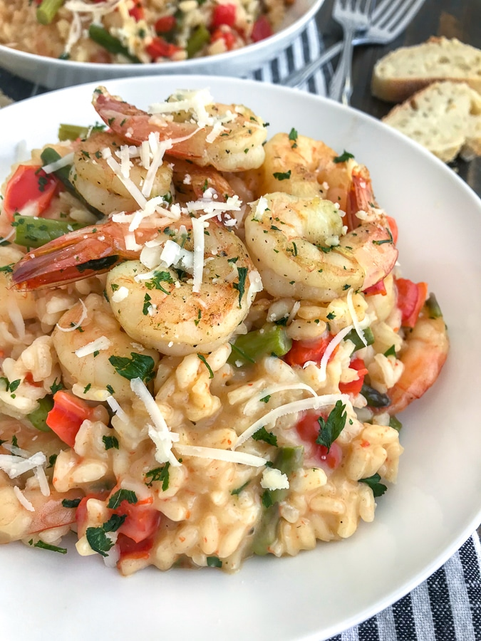 This Garlic Butter Shrimp with Asiago Risotto recipe is the perfect date night meal! Comes together in one pot, is bursting full of flavor and is so easy to make. I guarantee your taste buds will be floored! #risotto #garlicbuttershrimp #asiagorisotto   https://withpeanutbutterontop.com