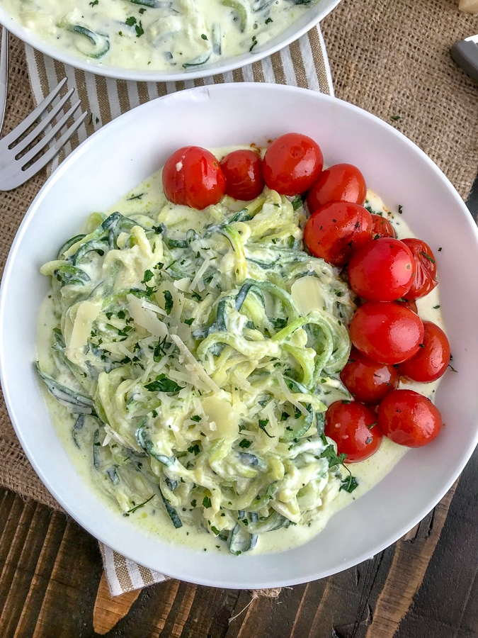 A light, fresh and easy dinner that will curb any creamy pasta craving! Cooked, tender zucchini noodles tossed in a creamy, garlic parmesan ricotta sauce and served with a side of blistered cherry tomatoes. The perfect healthy dinner option! #zoodles #parmesanzoodles   https://withpeanutbutterontop.com