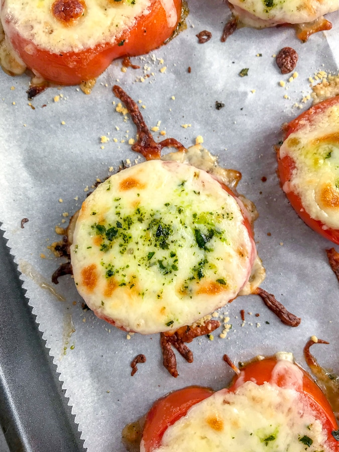 Easy sheet pan appetizer for tomato slices baked with mozzarella and parmesan cheeses.