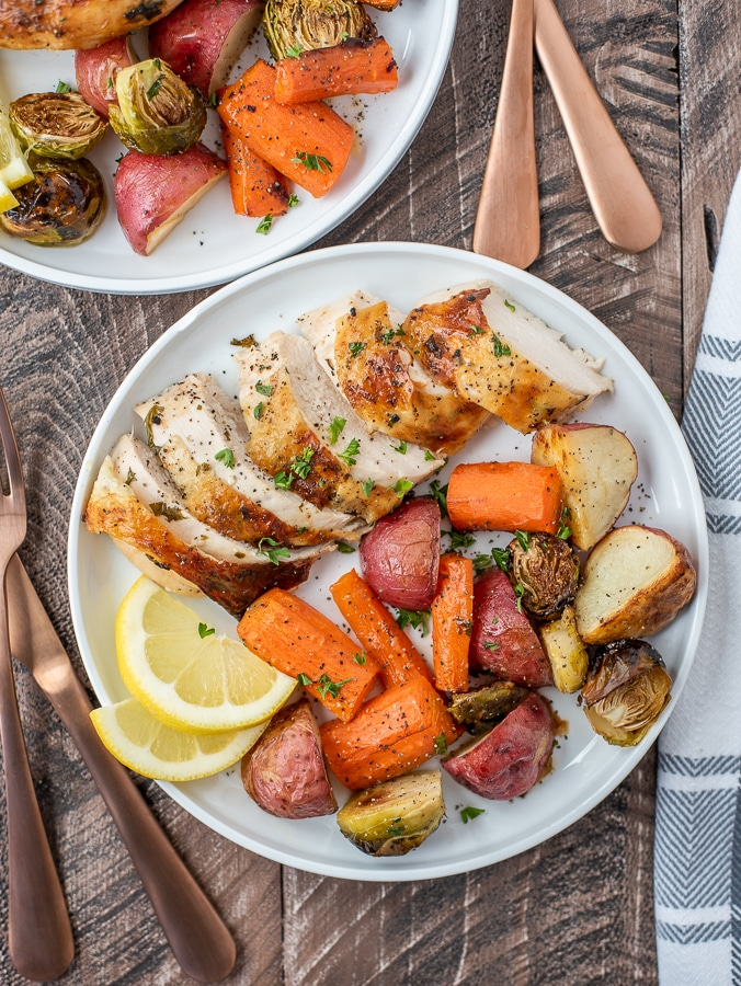 Lemon Garlic Butter Butterfly Chicken and Veggies. Dinner plate filled with sliced chicken and vegetables.