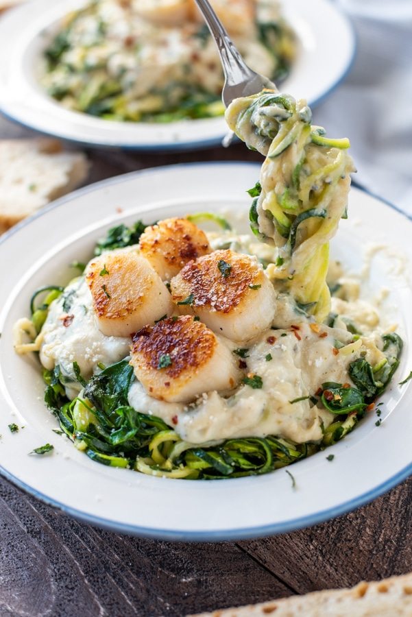 White bowl filled with Pesto Spinach Cauliflower Alfredo with Scallops.