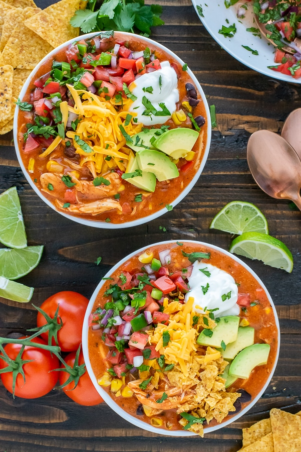 Bowl filled with a Mexican soup and garnished with avocado, greek yogurt, cheddar cheese and pico de gallo.