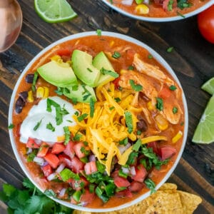 Bowl filled with chicken enchilada soup and garnished with avocado, greek yogurt, cheddar cheese and pico de gallo.
