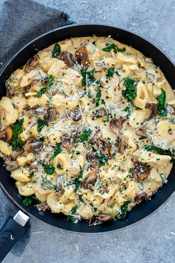 Pan filled with tortellini, mushrooms, and spinach.