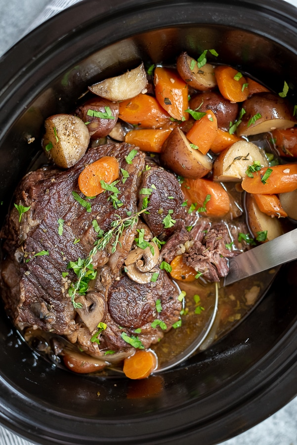 Crock pot filled with pot roast, potatoes, carrots, and mushrooms.