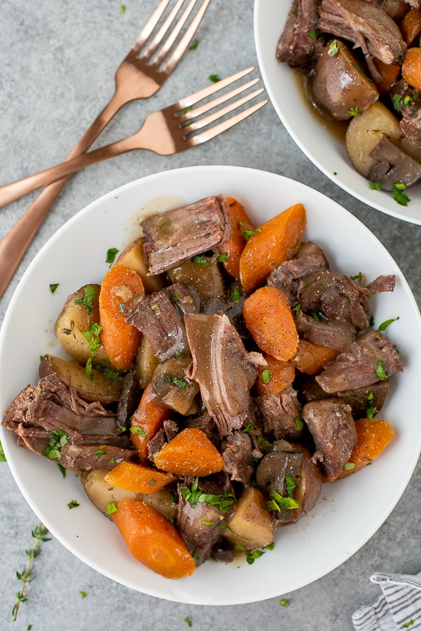 White bowls filled with pot roast, carrots, mushrooms and potatoes.