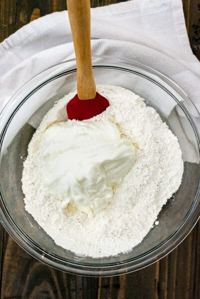 Clear mixing bowl filled with flour and greek yogurt.