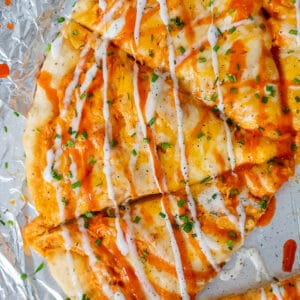 Buffalo Ranch Chicken Pizza sliced and garnished with buffalo sauce, ranch dressing and chopped chives.